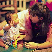Infant and teacher interacting with toys
