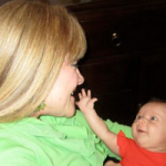 Infant reaching out to caress parent's face
