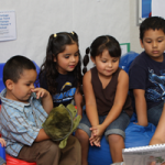 Children sitting and listening to teacher reading a book
