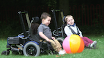 children in wheelchairs chasing a beach ball