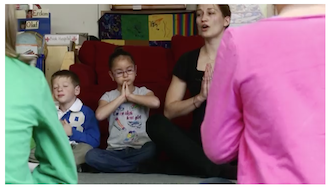 Children in classroom meditating with teacher