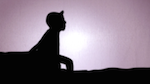 Silhouette of a child sitting on a bench