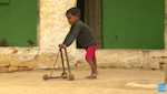 A child using a homemade wooden walker