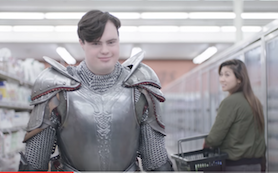 Girl admiring boy grocery shopping while wearing suit of armor