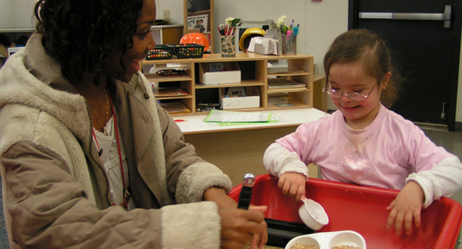 Teacher and student with down syndrome interacting at activity table