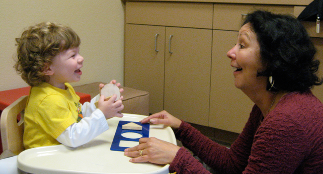 Teacher engaging with child during classroom activity. Link to Early Identification page.