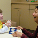 Teacher engaging with child during classroom activity