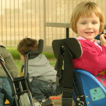 Children on play ground using assistive devices