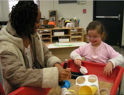 Teacher and student interacting at activity table