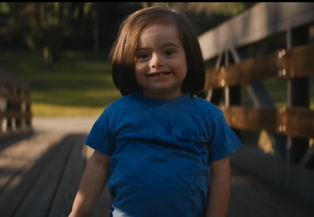 Child with down syndrome walking on a bridge