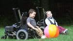 children in wheelchairs chasing a beach ball