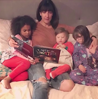 Mother reading to her three children