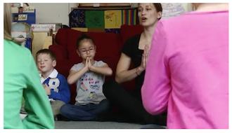 Children in classroom meditating with teacher