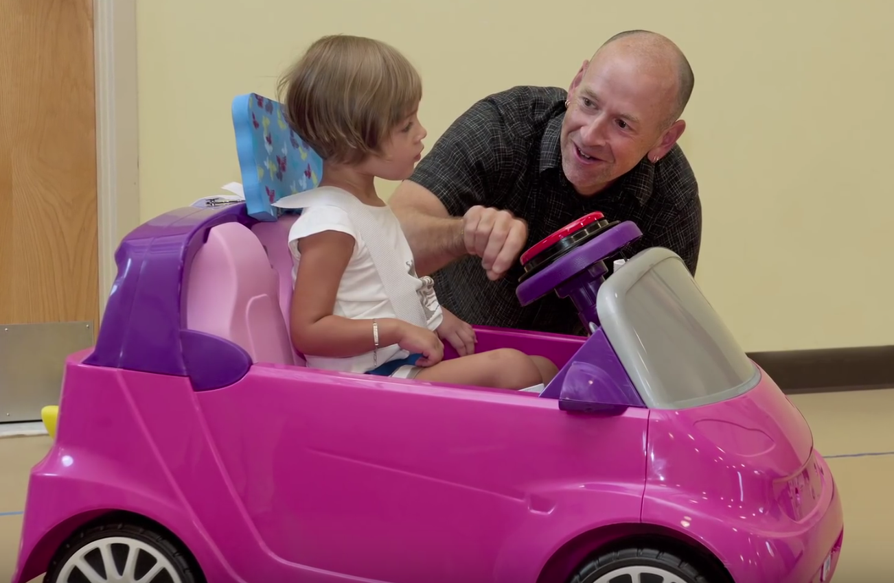 Man talking to child sitting in an adapted motorized toy car