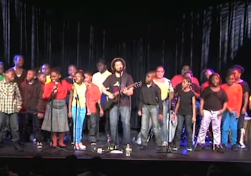 Large group of children on stage singing