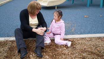 Teaching and student sitting and talking in playground