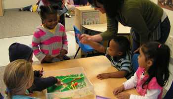 Teacher assisting students with an art project during class