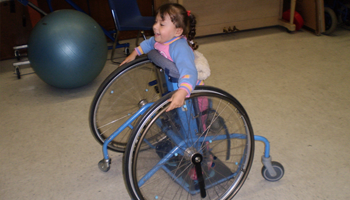 Child using an assistive device to move around classroom