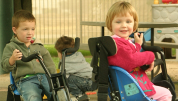 Children riding tricycles on playground