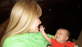 Infant reaching out to caress parents face