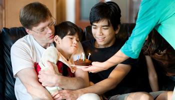 Father holding son with cerebral palsy while mother serves birthday cake. Older brother watches.