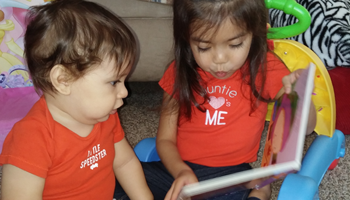 Young child reading a book to a toddler