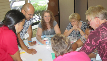 Teachers working together on an activity around a table