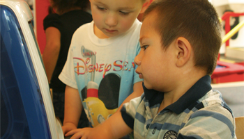 Two children interacting with a computer